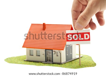 "Hand holding ""sold""-sign in front of model house - real estate buying concept"
