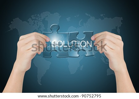 hand holding solution connected jigsaw puzzle with world map background