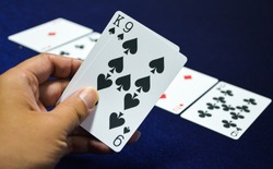 Hand holding 9 Spade and  king of spade card on poker game.playing poker cards game.