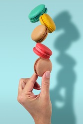 Hand holding stack of colorful French macaroons on light blue background