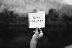 Hand holding stay focused text