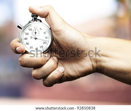 hand holding stopwatch against a abstract background