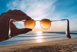 Hand holding stylish round sunglasses with brown lenses at sunset. Putting on sunglasses at sunny summer day near the ocean. Man looking at bright sun through polarized sunglasses. Summer vibes