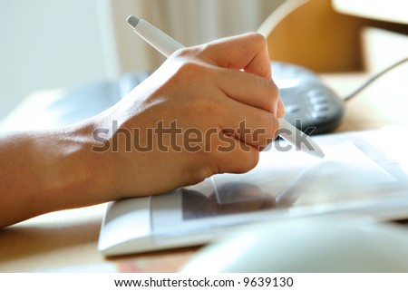 Hand holding stylus pen while working on tablet attached to computer.
