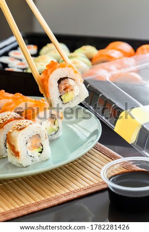 Hand holding sushi roll with chopsticks. Salmon roll topping with caviar. Traditional Japanese seafood sushi roll.  Fresh Sashimi. asian food. Fresh salmon. Sushi delivery. Lunch. Take away food