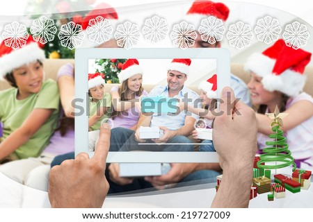 Hand holding tablet pc against snowflake frame
