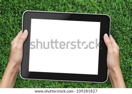 Hand holding tablet pc. over green grass background.