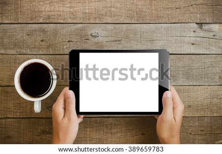 hand holding tablet similar to ipades style on wood table