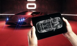 Hand holding tablet with car outline in blurry garage with red sportscar. Transport diagnostics and innovation concept