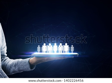 Hand holding tablet with glowing social network on dark background. Networking and HR concept