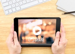 Hand holding tablet with Video sharing on screen on wood table ,Internet marketing concept.