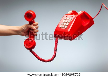 Hand holding telephone, classic red telephone receiver, old telephone isolated on white background flying in weightlessness. #1069895729