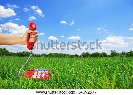 Hand holding telephone over the meadow