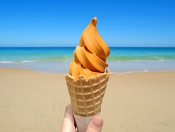 Hand holding Thai tea soft serve ice cream in a waffle cone on beautiful beach background in summer