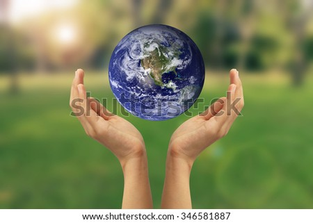 Hand holding the blue Earth. Elements of this image furnished by NASA
