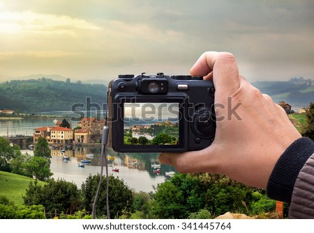 hand holding the Digital camera, shoot of landscape photo using liveview