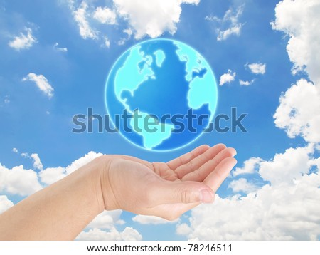 Hand holding the earth against blue sky