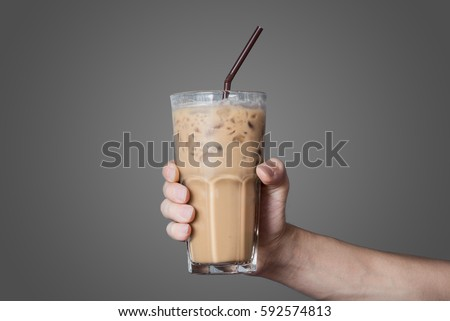 Hand holding the glass of cold coffee with grey background #592574813