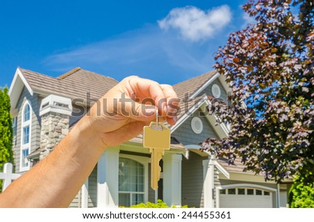Hand holding the keys for a big custom made luxury house for sale, house of dream in the suburbs of Vancouver, Canada. Horizontal.