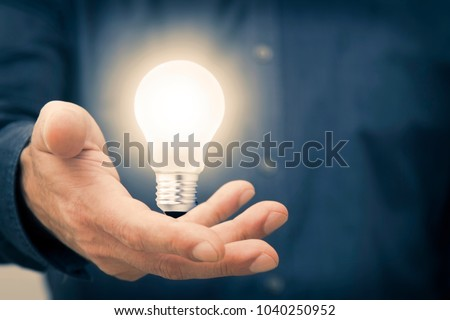 hand holding the light bulb on, concept of idea and creativity #1040250952