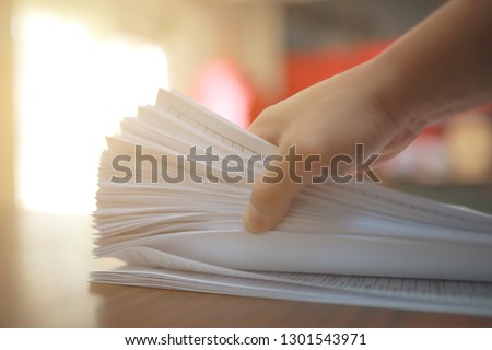 Hand holding the Paper business documents of unfinished stacked on office desk archive,in archive analyzing the market and considers on the size of future profits on table office and have Orange light