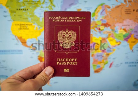 Hand holding the passport of Russia against the colorful world map atlas. Russian passport concept, Russian tourists travel concept. #1409654273