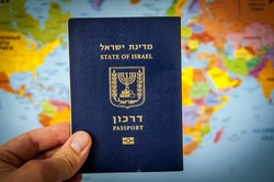 Hand holding the passport of the State of Israel against the colorful world map atlas. Israel citizenship concept, Israeli biometric
