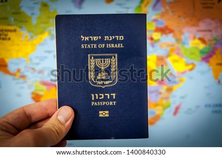 """Hand holding the passport of the State of Israel against the colorful world map atlas. Israel citizenship concept, Israeli biometric """"darkon"""" passport illustrative image. Global travel concept. #1400840330"""