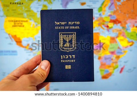 "Hand holding the passport of the State of Israel against the colorful world map atlas. Israel citizenship concept, Israeli biometric ""darkon"" passport benefits illustrative image. Global travel. #1400894810"