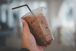 Hand holding the plastic cup of cold Mocha coffee. Close up