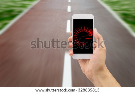 hand holding the smart phone with tachometer speed in the screen over the road in background Foto stock ©