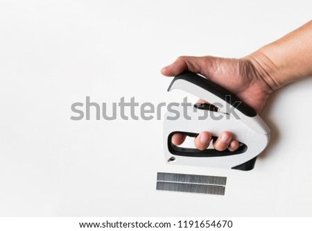 Hand holding the Stapler and Strip of the Staples with copyspace