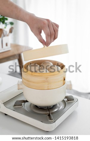 Hand holding the steamer cover that is steaming the steamed bread #1415193818
