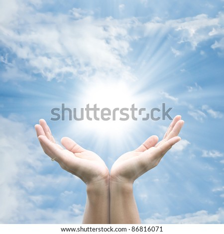 Hand holding the sun - stock photo