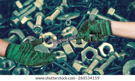 hand holding the wrench on used nut and bolts for equipment industrial background