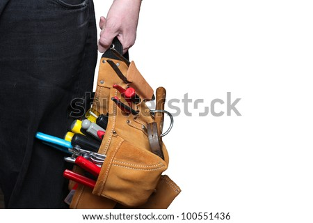 Hand Holding Toolbelt. Suede tool puch belt filled with tools & a nylon belt hanging from man's left hand against black denim trousers & isolated background. Clipping path included.