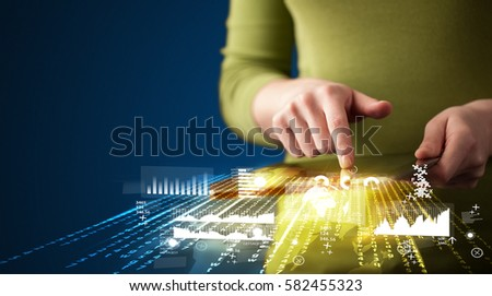 Hand holding touchpad tablet with business market graphs and icons concept on background #582455323