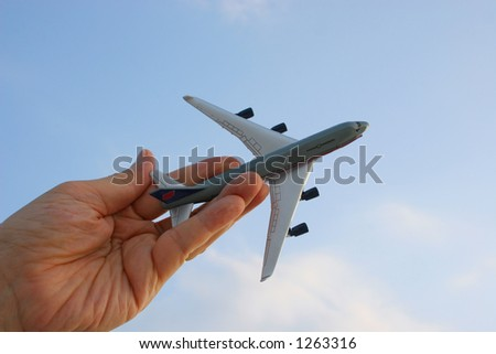 Hand holding toy plane in the sky.