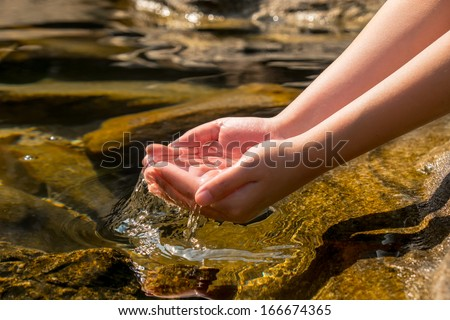 hand holding transparent clear water from natural well