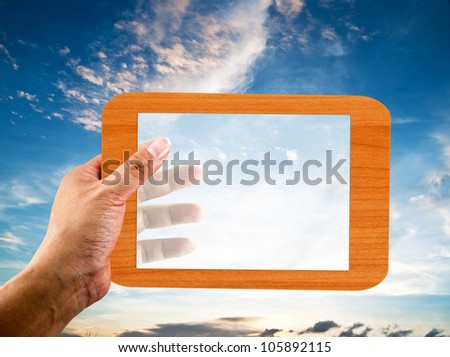 Hand holding transparent wooden frame with nice sky