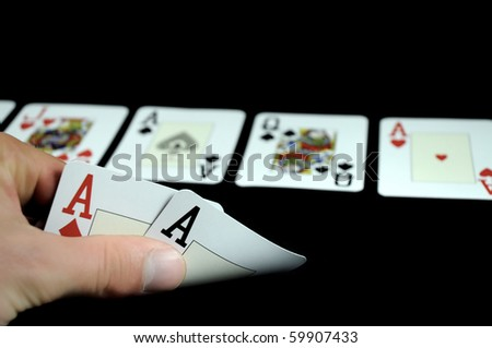 hand holding two aces cards and board with five cards isolated on black