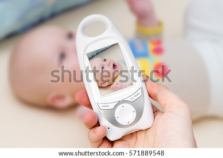 Hand holding video baby monitor for security of the baby #571889548