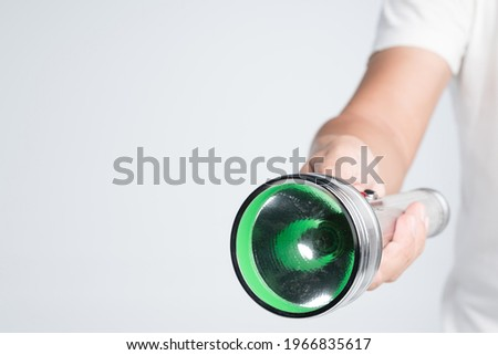 Hand holding vintage aluminium flashlight powered by size D batteries on white background Foto stock ©