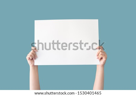 hand holding white blank paper isolated on blue background with clipping path Stock photo ©