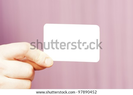 hand holding white business card on pink background