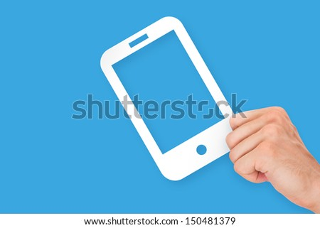 Hand holding white, empty, blank mobile phone cardboard, isolated on blue background.