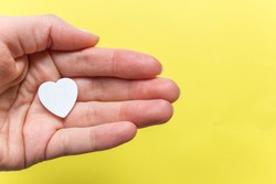 hand holding white heart on yellow background. Top view, layout. Free copy space. Concept of love, care and solidarity.
