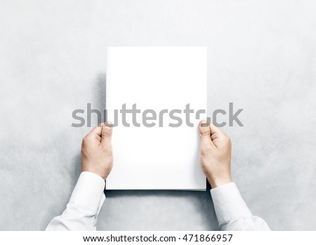Hand holding white journal with blank cover mockup. Arm in shirt hold clear magazine template mock up. A4 book softcover surface design. Paperback print display show. Closed notebook cover showing. - Shutterstock ID 471866957