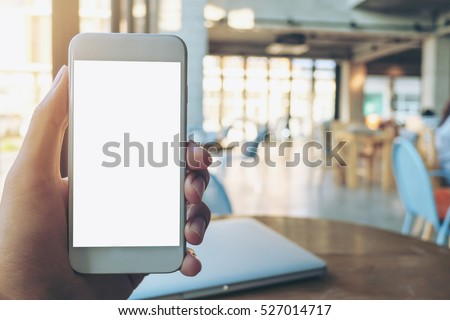Hand holding white mobile phone with blank white screen and silver laptop on vintage wood table in cafe