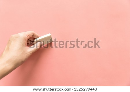 Hand holding white rubber for erasing something on empty pink background. Abstract background with copy space. Stok fotoğraf ©